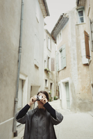 France, Languedoc-Roussillon, Sauve, Young tourist with camera in narrow street