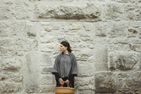 France, Languedoc-Roussillon, Sauve, Young woman standing by stone wall holding basket