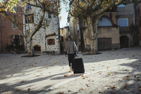 France, Languedoc-Roussillon, Sauve, Young woman walking with luggage across town square