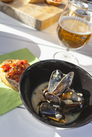 Sweden, Mussel soup, brushetta and beer glass on wooden table