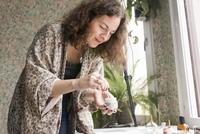 Sweden, Mature woman stirring glue