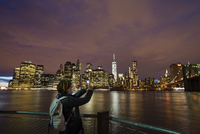 USA, New York State, New York City, Manhattan, Woman photographing skyline with smart phone 11090015061| 写真素材・ストックフォト・画像・イラスト素材|アマナイメージズ
