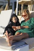 Spain, Gran Canaria, Maspalomas, Mother and son (2-3) using smart phone