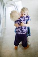 Two sisters (2-3) hugging