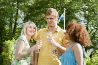 Young people standing with wine glasses in sunlight