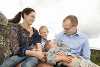 Sweden, Vastra Gotaland, Torslanda, Family with two children (4-5) sitting on rock