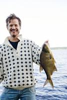 Sweden, Dalarna, Svardsjo, Smiling man holding caught fish by lake