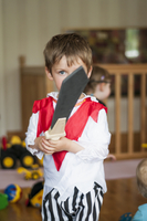 Boy (4-5) dressed as knight playing with toy sword