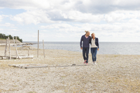 Sweden, Gotland, Bungenas, Couple walking side by side along beach by Baltic sea