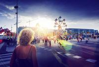 Sweden, Skane, Malmo, Anna Lindhs Plats, Woman crossing city street towards travelling carnival ground 11090017084| 写真素材・ストックフォト・画像・イラスト素材|アマナイメージズ