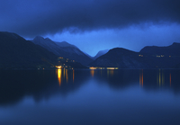 Norway, More og Romsdal, Eidsdal, Still lake and reflections of illuminated towns on opposite shore