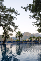 Turkey, Mugla, Marmaris, Swimming pool in holiday resort and mountains in background