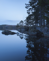 Sweden, Vastergotland, Tiveden National Park, Stora Trehorningen, Reflection of trees in lake at sunset 11090017425| 写真素材・ストックフォト・画像・イラスト素材|アマナイメージズ