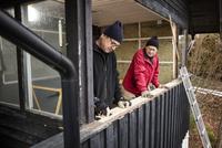 Sweden, Uppland, Rindo, Men building wooden balustrade