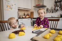 Sweden, Two boys (18-23 months, 4-5) baking saffron buns