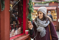Sweden, Stockholm, Gamla Stan, Woman using phone at market