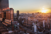 Japan, Tokyo, Shibuya, View of city at sunset from window
