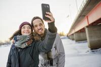 Sweden, Vasterbotten, Umea, Young couple taking selfie by bridge in winter 11090017699| 写真素材・ストックフォト・画像・イラスト素材|アマナイメージズ