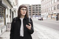 Sweden, Skane, Malmo, Young woman using mobile phone in street 11090017761| 写真素材・ストックフォト・画像・イラスト素材|アマナイメージズ