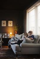 Denmark, Boy (8-9) and girl (4-5) sitting on sofa in living room 11090017784| 写真素材・ストックフォト・画像・イラスト素材|アマナイメージズ