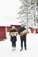 Finland, Jyvaskyla, Saakoski, Young couple standing and holding firewood with houses in background 11090017895| 写真素材・ストックフォト・画像・イラスト素材|アマナイメージズ