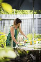 Sweden, Uppland, Woman setting table in garden 11090017961| 写真素材・ストックフォト・画像・イラスト素材|アマナイメージズ