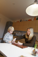 Sweden, Mother and son (2-3) wrapping presents for Christmas 11090018010| 写真素材・ストックフォト・画像・イラスト素材|アマナイメージズ