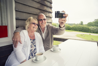 UK, England, Lincolnshire, Louth, Senior couple sitting at table on porch and taking selfie with camera 11090018168| 写真素材・ストックフォト・画像・イラスト素材|アマナイメージズ