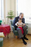 Finland, Senior man sitting in armchair and holding grandson (18-23 months) on laps