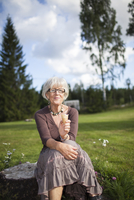 Sweden, Medelpad, Portrait of senior woman sitting on tree stump and eating ice-cream