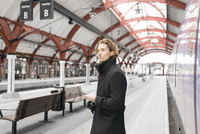 Sweden, Skane, Malmo, Businessman texting at railroad station 11090018502| 写真素材・ストックフォト・画像・イラスト素材|アマナイメージズ