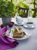 Sweden, Plum tart on plate, coffee cup and milk on table 11090018548| 写真素材・ストックフォト・画像・イラスト素材|アマナイメージズ