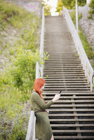 Finland, Pirkanmaa, Tampere, Redhaired woman standing on staircase and using phone 11090018832| 写真素材・ストックフォト・画像・イラスト素材|アマナイメージズ