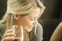 Sweden, Blonde woman laughing and drinking red wine 11090019145| 写真素材・ストックフォト・画像・イラスト素材|アマナイメージズ