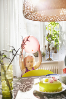 Sweden, Girl (2-3) standing by table and holding balloon 11090019229| 写真素材・ストックフォト・画像・イラスト素材|アマナイメージズ