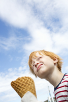 Sweden, Low angle view of redhead boy (6-7) eating ice cream against sky 11090019359| 写真素材・ストックフォト・画像・イラスト素材|アマナイメージズ