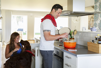Sweden, Man cooking and woman playing with dog in kitchen 11090019367| 写真素材・ストックフォト・画像・イラスト素材|アマナイメージズ