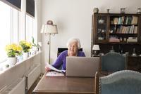 Sweden, Senior woman with laptop sitting in living room 11090019544| 写真素材・ストックフォト・画像・イラスト素材|アマナイメージズ