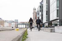 Sweden, Skane, Malmo, Rear view of woman and man cycling 11090019609| 写真素材・ストックフォト・画像・イラスト素材|アマナイメージズ
