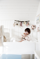 Sweden, Small girl (2-3) sitting in bed and embracing doll 11090019725| 写真素材・ストックフォト・画像・イラスト素材|アマナイメージズ