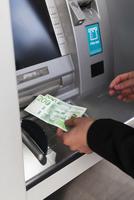 Sweden, Stockholm, Woman taking money from ATM 11090019848| 写真素材・ストックフォト・画像・イラスト素材|アマナイメージズ