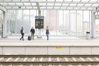Sweden, Vasterbotten, Umea, Woman and men on railroad station platform 11090020023| 写真素材・ストックフォト・画像・イラスト素材|アマナイメージズ