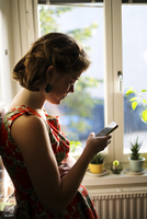 Sweden, Young woman texting on smart phone 11090020172| 写真素材・ストックフォト・画像・イラスト素材|アマナイメージズ