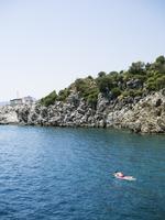 Turkey, Mugla, Marmaris, Man floating on mattress by rocky coast 11090020185| 写真素材・ストックフォト・画像・イラスト素材|アマナイメージズ