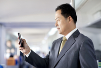 Mature businessman with smart phone in subway train