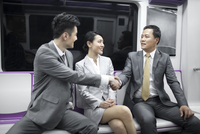 Cheerful business people shaking hands in subway train