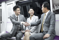 Business persons shaking hands in subway train