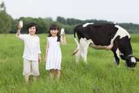 Happy children holding glasses of milk with cattle grazing i