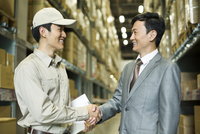 Young logistics staff shaking hands with businessman