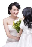 Cute daughter giving flowers to mother
